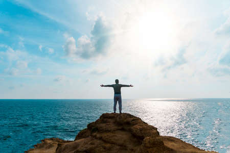 Man rise hands up to sky freedom concept with blue sky and summer beach ocean background. Imagens