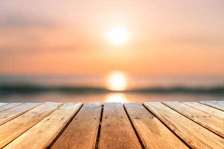 Messa a fuoco selettiva del vecchio tavolo in legno con sfocatura del bellissimo sfondo della spiaggia per visualizzare il prodotto. Archivio Fotografico