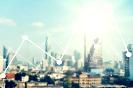 Blur capital town many buildings and people in city with transportation system double exposure graph uptrend or downtrend and technology icon  with sunlight background.