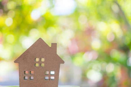 Modello domestico minuscolo chiuso sul pavimento o sul bordo di legno con il fondo del bokeh verde di luce solare. La vita di Deam ha una proprietà di casa propria per vivere o un concetto di investimento.