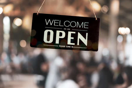 A business sign that says open on cafe or restaurant hang on door at entrance. Vintage color tone style.
