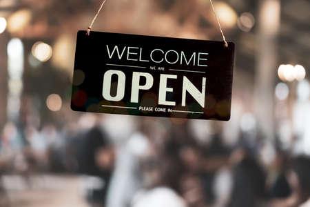 Een bedrijfsbord met de tekst open op café of restaurant hangt aan de deur bij de ingang. Vintage kleurtoon stijl.