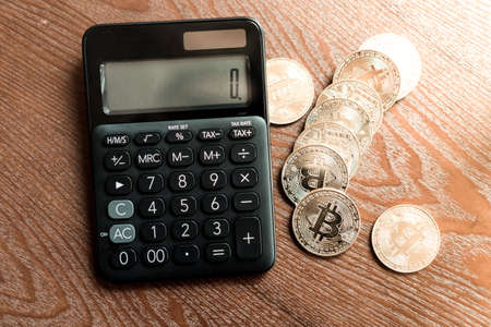 Calculator and a stack of Bitcoins coins as symbol of cryptocurrency digital money in the future blockchain. Wealth rich investment concept.