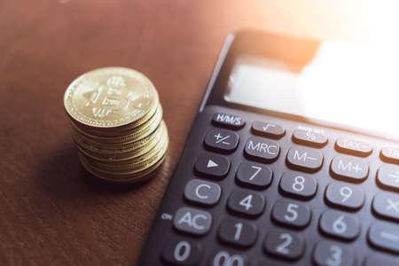 Calcolatrice e una pila di monete Bitcoin come simbolo di denaro digitale di criptovaluta nella futura blockchain. Concetto di investimento ricco di ricchezza. Archivio Fotografico