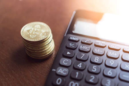 Rekenmachine en een stapel Bitcoins-munten als symbool van cryptocurrency digitaal geld in de toekomstige blockchain. Rijkdom rijk investeringsconcept. Stockfoto
