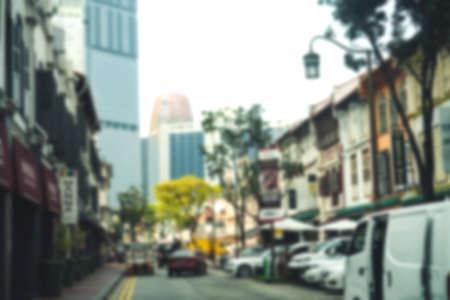 Bâtiment d'architecture sino-portugaise floue en ville avec une tonalité de couleur de style vintage avec une ambiance de voyage de voyageur faisant du shopping à l'arrière-plan de la rue piétonne. Banque d'images