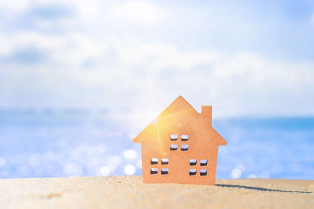 Closed up tiny home models on sand with sunlight and beach background.Investment property concept.