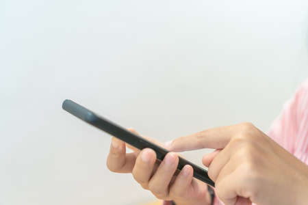 Woman hand use smartphone to do work business, social network, communication in public space.