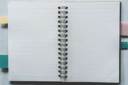 Top view of blank space white notebook and pen with tropical leaf as frame background.