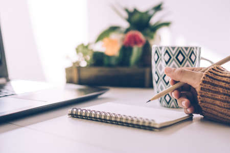 Woman hand write down in white memo notebook for take a note not to forget, to do list or plan for work in future on work desk.