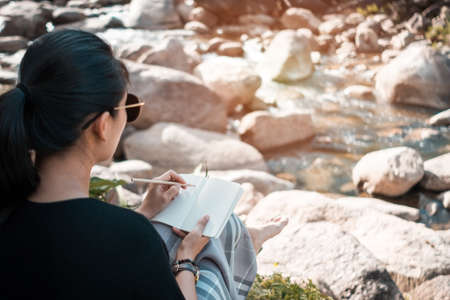 Woman is writing down in small white memo notebook for take a note not to forget, plan to do or write a book with beautiful terrace of house and nature mountain view background. 스톡 콘텐츠
