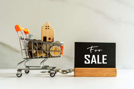 Home model in mini cart model full of coins money with for sale text on blank black wooden sign background.