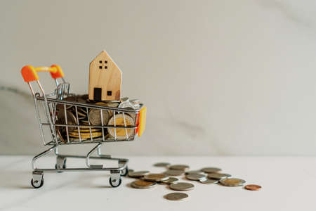 Home model in mini cart model full of coins money with copyspace white background. Фото со стока
