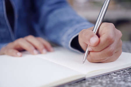 Copy space of woman hand writing down in white notebook with colorful bokeh background. 스톡 콘텐츠