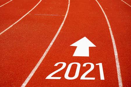 La ligne de départ jusqu'en 2021 sur le terrain de course représente le début d'un voyage vers la destination en matière de planification d'entreprise, de stratégie et de défi ou de cheminement de carrière, concept d'opportunité.