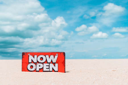 Now open sign board stand on sand summer beach background metaphor to time to travel relax tourism season with copyspace background.