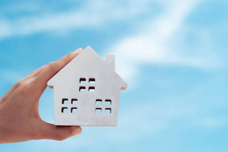 Copyspace with model of a little house that woman holds it background. Dream family life concept.