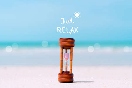 Just relax qoute with hourglass on sand and summer beach blue sky background. Time to travel tourism season concept background. Imagens
