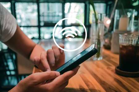 Woman hand using smartphone with wifi icon in cafe shop background. Business communication social network concept. Foto de archivo