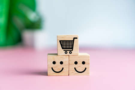 Smile face and cart icon on wood cube. Optimistic person or people feeling inside and service rating when shopping, satisfaction concept in business. 免版税图像 - 151033758