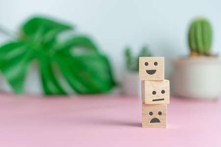 Smile face and cart icon on wood cube. Optimistic person or people feeling inside and service rating when shopping, satisfaction concept in business. 免版税图像 - 151034072