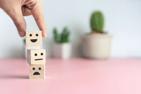 Smile face and cart icon on wood cube. Optimistic person or people feeling inside and service rating when shopping, satisfaction concept in business. 免版税图像 - 151034491