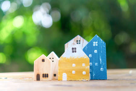 Closed up tiny home model on floor or wooden table with sunlight green bokeh background. Deam life have own house property for living or investment concept.