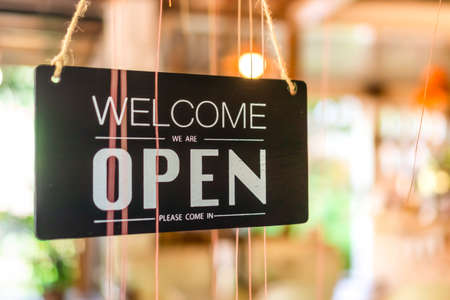 A business sign that says open on cafe or restaurant hang on tree at entrance of shop with sun light bokeh background