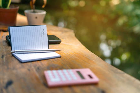 Memo book and calculator on wooden table with river on background. Фото со стока