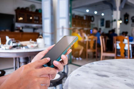 Man hand using smartphone to do work business, social network, communication in public cafe work space.