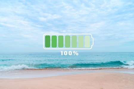 Fully charge battery 100% sign icon on natare summer beach on vacation day. Holiday long weekend relax time concept.