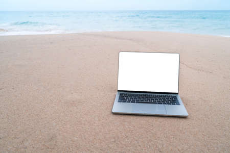 Laptop on sand at summer beach in background with white screen.
