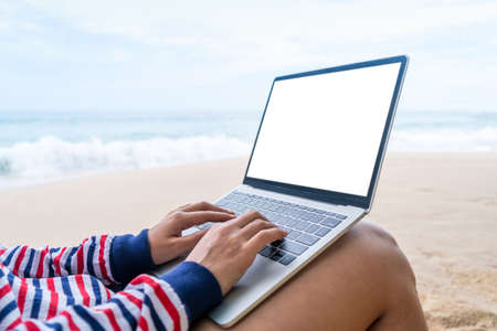 Woman using laptop and smartphone to work study in vacation day at beach background. Business, financial, trade stock maket and social network concept.