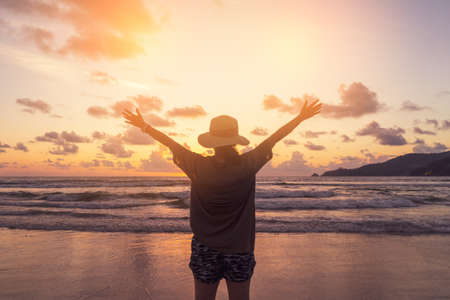 Woman rise hands up to sky freedom concept with sunset sky and summer beach season background.