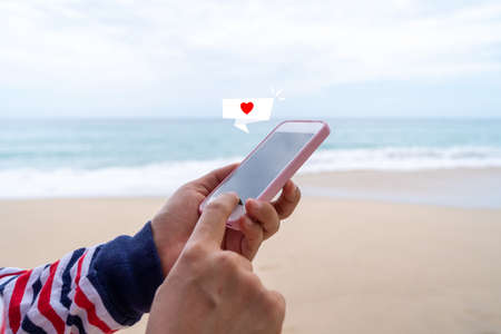 Heart sign on chat box icon on smartphone at summer beach technology concept.