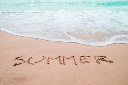 Summer word hand drawn on sand summer beach background. 免版税图像