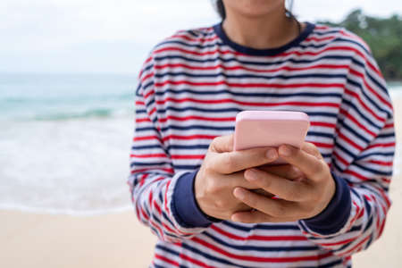 Woman using smartphone to work study in vacation day at beach background. Business, financial, trade stock maket and social network concept.