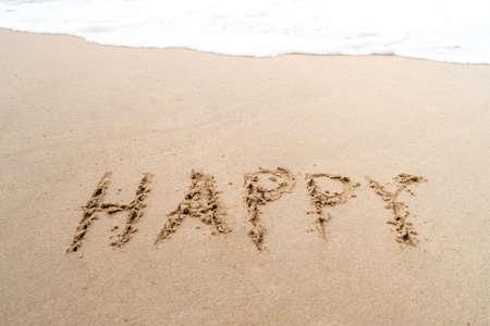 Happy word hand drawn on sand summer beach background. 免版税图像