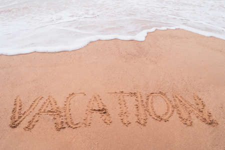 Vacation word hand drawn on sand summer beach background. 免版税图像 - 155183045