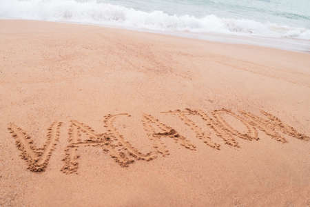 Vacation word hand drawn on sand summer beach background. 免版税图像