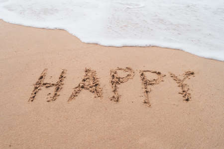 Happy word hand drawn on sand summer beach background. Archivio Fotografico