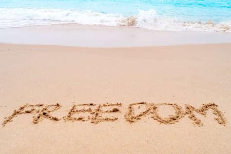Freedom word hand drawn on sand summer beach background. 免版税图像