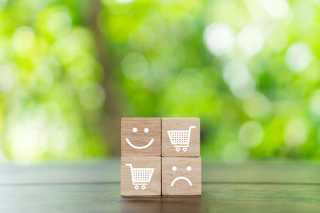 Smile face and cart icon on wood cube. Optimistic person or people feeling inside and service rating when shopping, satisfaction concept in business. 免版税图像 - 155122750