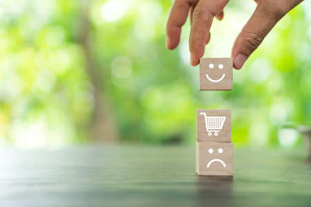 Smile face and cart icon on wood cube. Optimistic person or people feeling inside and service rating when shopping, satisfaction concept in business. 免版税图像 - 155122701