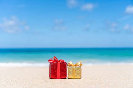 Gift boxes on sandy beach. Hot tours or holiday vacation concept with summer sea background.