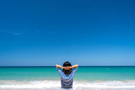 Woman rise hands up to sky freedom concept with blue sky and summer beach background. 免版税图像