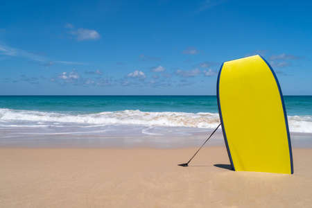 Small surfboards on sand at summer beach with sun light and blue sky background. 免版税图像