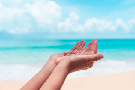 Woman hands place together like praying in front of nature clean beach and blue sky background. Foto de archivo