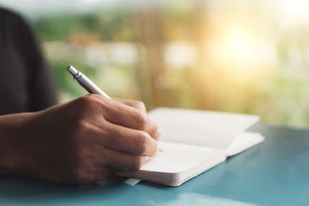 Woman hand writing down in small white memo notebook for take a note not to forget or to do list plan for future. Banque d'images
