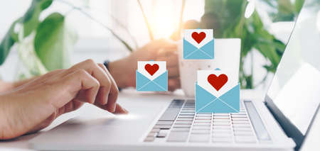 Hand typing keyboard with laptop computer with social media love letter mail send out icons valentine concept. 免版税图像